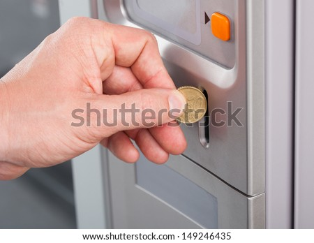 Close-up of human hand inserting coin in vending machine