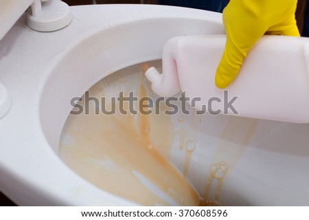 Close up of human hand pouring detergent from bottle into toilet bowl for cleaning and disinfection