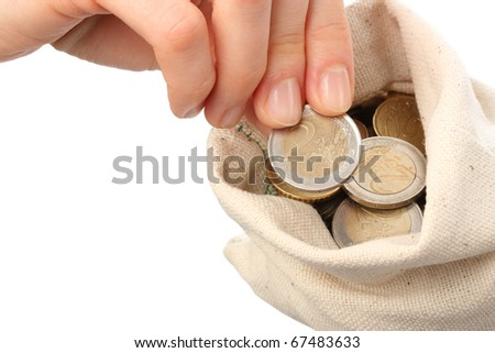 Close-up of human hand putting coin into a sack isolated on white