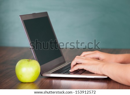 Close-up of human hand using laptop on desk - stock photo
