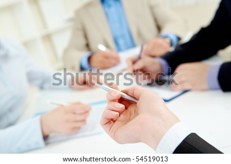 Close-up of human hand with pen pointing at document