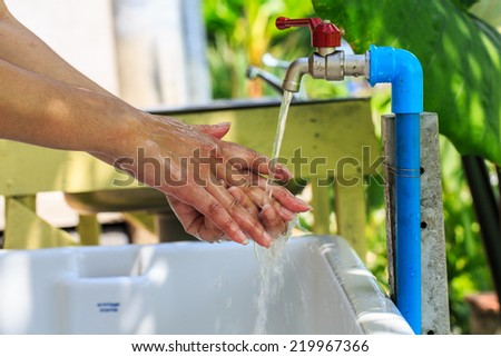 Close-up of human hands being washed under stream of water from tap - stock photo