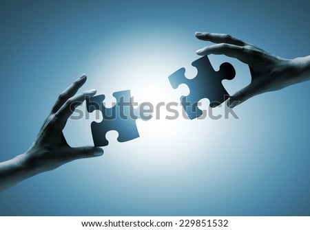 Close up of human hands connecting puzzle elements - stock photo