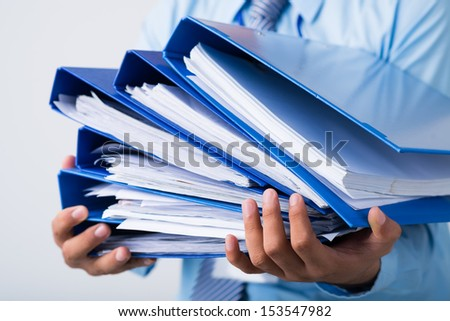 Close-up of human hands holding a stack of folders with business documents on the foreground - stock photo