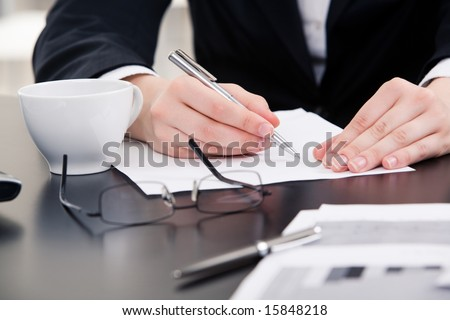 Close-up of human hands holding pen over paper ready to write with cup glasses and document near by - stock photo