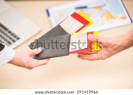 Close-up of human hands holding tickets and passports. - stock photo