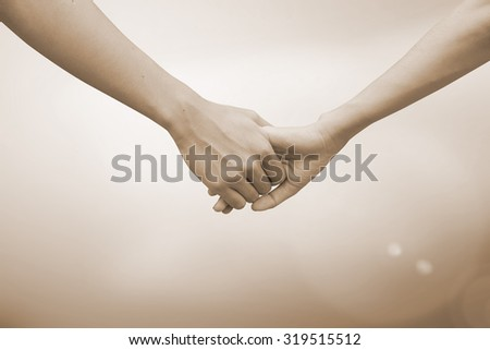 close up of human hands holding together for helping and cheer up : helping hands concept :family and friends concept.hand of power family.abstract helping hand in sepia vintage tone colors concept. - stock photo