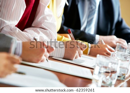 Close-up of human hands over business documents during conference - stock photo