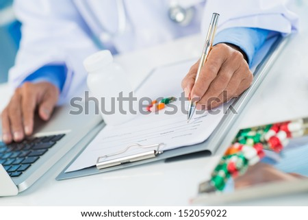 Close-up of human hands prescribing medicaments on the foreground - stock photo