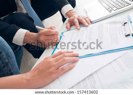 Close-up of human hands signing a contract on the foreground - stock photo