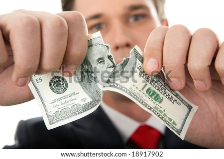 Close-up of human hands tearing hundred-dollar banknote - stock photo