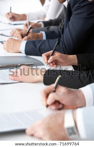 Close-up of human hands with pens over business documents - stock photo