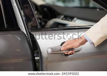 Close up of human male hand opening car door - stock photo