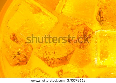 Close-up of ice cubes in orange juice