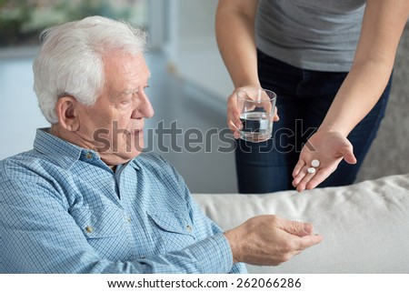 Close-up of ill senior man taking medicine - stock photo