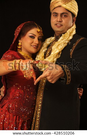 Close up of Indian couple's hands at a wedding - stock photo