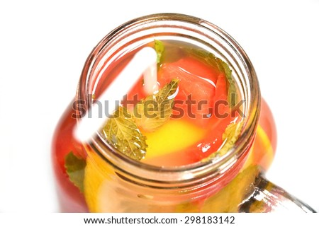 Close up of Infused water in a mason jar isolated on white background. Consisting of watermelon, lemon and mint. - stock photo