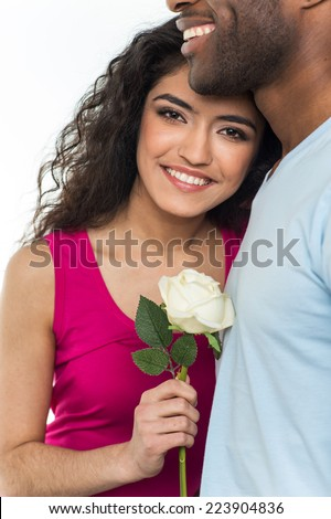 Close up of interracial couple holding white rose. African American man and indian woman looking into camera - stock photo