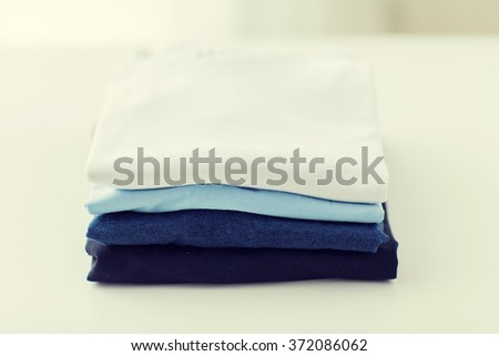 close up of ironed and folded t-shirts on table - stock photo
