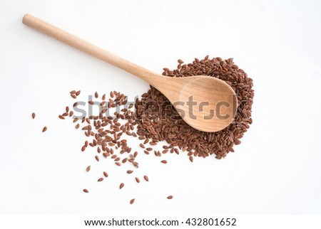 close up of isolated flax seed on white background - traditional wooden spoon - studio shot from above