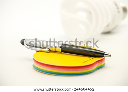 Close up of isolated note paper or notepad for writing with pen and light bulb for idea background  - stock photo