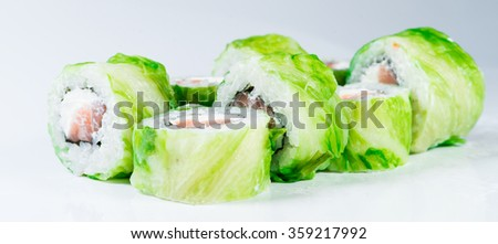 close-up of  Japan sushi roll with salmon and lettuce (shallow DOF) on a white background - stock photo