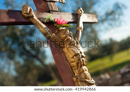 Close up of Jesus Christ crucifixion sculpture against blue sky. Religion, belief and hope concept. - stock photo