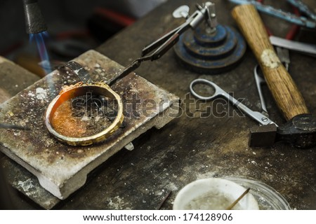 Close up of Jeweler crafting golden bracelet with flame torch.
