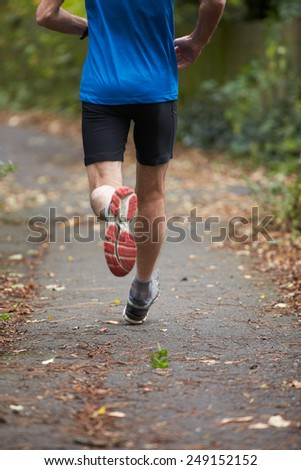 Close Up Of Jogger's Feet Running On Path - stock photo