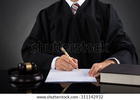 Close-up Of Judge Writing On Paper With Pen In Courtroom - stock photo
