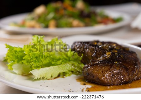 Close Up of Juicy Steak on Plate with Garnish on Restaurant Table - stock photo