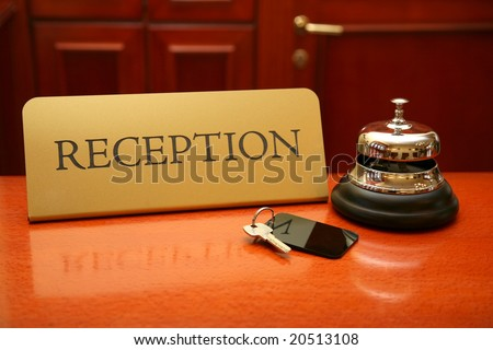 Close up of key and bell on wooden reception desk - stock photo