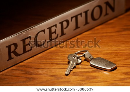 Close up of key on wooden reception desk. - stock photo