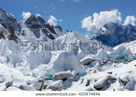 Close up of Khumbu glacier in Everest Base Camp, Himalayas, Nepal. Clear turquoise glacier ice blocks lit by a bright sun light on a sunny day. Stunning Himalayan glacier close up. - stock photo