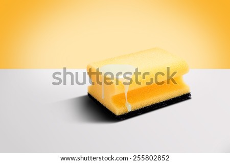 Close up of kitchen sponge for dishes on white background with detergent on it - stock photo