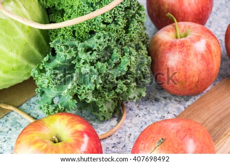 Close up of kitchen table with ripe apples, kale and green cabbage from farmers market. - stock photo