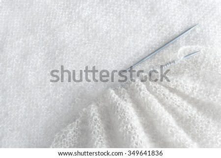 Close-up of knitting needles and white yarn. - stock photo