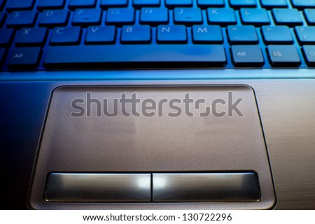 close up of laptop keyboard as a background toned to blue - stock photo