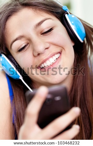 Close up of laughing teenager girl with smartphone - stock photo