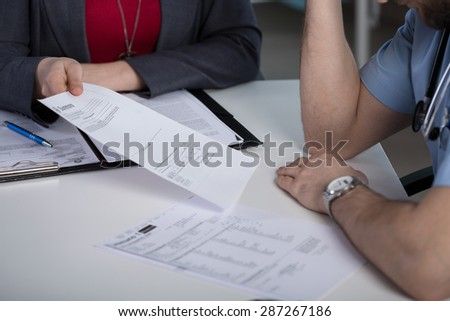 Close-up of lawyer giving the summons to young doctor - stock photo