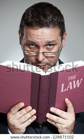 Close-up of lawyer in suit holding and reading book.