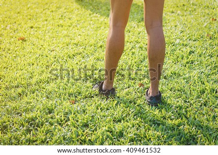 Close up of left sneaker with legs of male runner standing on grass in park - stock photo