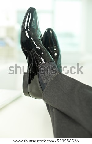Close-up of legs in elegant business shoes relaxing in office