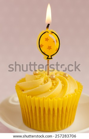 close up of Lemon cupcake with butter cream swirl and  single yellow alight balloon candle - stock photo