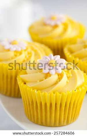 Close up of Lemon cupcakes with butter cream swirl and fondant flower decorations - stock photo