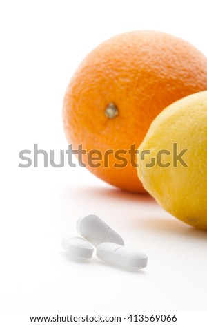 Close up of lemon, orange and pills isolated - vitamin concept  - stock photo