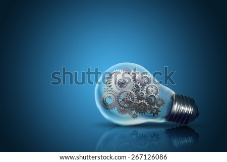 Close up of light bulb with gear mechanism inside isolated on dark blue background   - stock photo