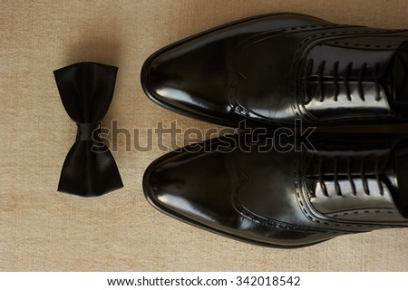close-up of lightened with natural light men's shoes and bow tie. Shoes and bow tie lying on the wooden floor. They are black - stock photo