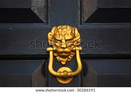 Close-up of lion headed door knocker on painted wooden door - stock photo