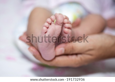 close up of Little baby feet with mother hand, baby is a asian - stock photo
